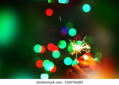 christmas sparklers over dark background with green, red, blue lights