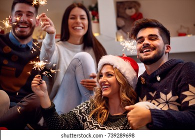 Christmas sparklers-happy friends enjoying party on Christmas