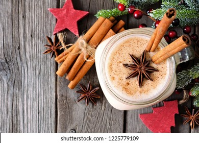 Christmas spiced eggnog in a mason jar. Above view with decorations on a rustic wood background.