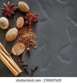 Christmas spices background, top view, flat lay on dark slate with copy space.  Cinnamon, nutmeg, star anise and cloves.