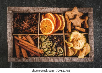 Christmas spices for baking, cocktails, mulled wine, with gingerbread cookies (stars) - dried apple, orange, cardamom, cloves, cinnamon, anise.  old wooden box, black stone table. copy space top view