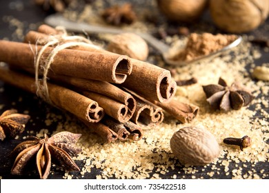 Christmas spices and baking ingredients. Cinnamon sticks, anise stars, nutmeg, cardamom, cloves, brown sugar and cocoa powder for Christmas cake, cookies or mulled wine.