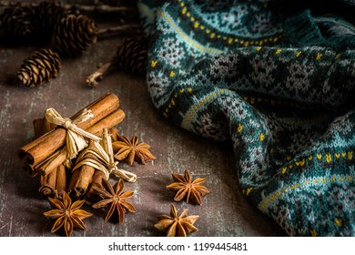 Christmas spices (star anise, cinnamon sticks for festivity) and warm knitwear on rustic background