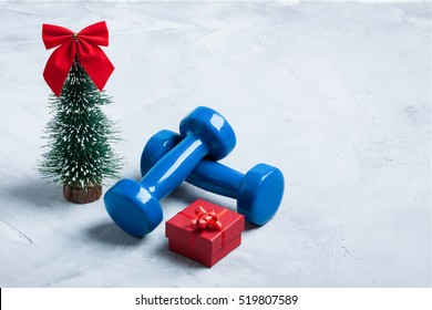 Christmas sport composition with dumbbells, red gift box and  christmas tree with red bow  on gray concrete background. Concept C�hristmas special for healthy lifestyle and sport.
