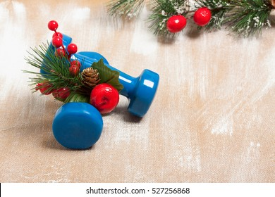 Christmas sport composition with dumbbells, red berries and  spruce on plywood background. Concept C�hristmas special for healthy  lifestyle and sport.