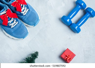Christmas sport flat lay composition with shoes, dumbbells, christmas tree and red gift  box on gray concrete background. Concept C�hristmas special for healthy lifestyle and  sport.