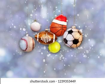 Christmas sports ornaments: baseball, football, basketball, and soccer ball hanging balls on snow background