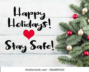 Christmas spruce branches with red golden decor on wooden table. Greeting card in times of covid pandemic with text Happy holidays, stay safe - Shutterstock ID 1866809242