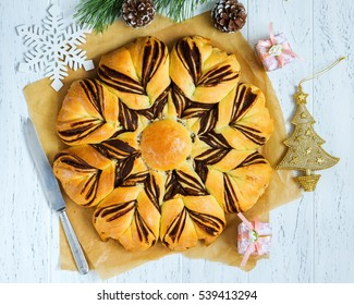 Christmas star braided chocolate bread on white wooden table.