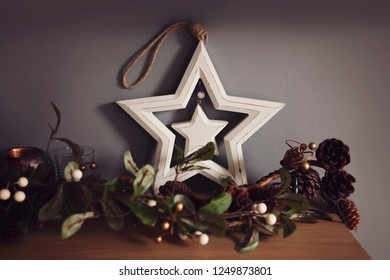 Christmas star decoration on a mantle wth a garland.
