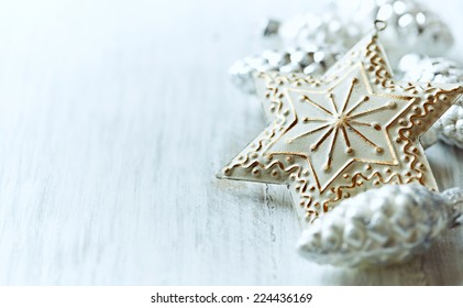 Christmas star and glass ornaments; close up. Bright wooden background.   Copy space.