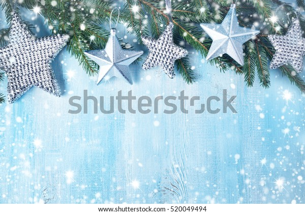 Christmas stars on wooden background with fir tree branches. Winter background