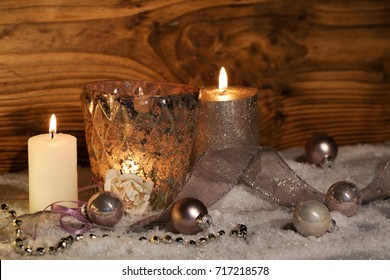 Christmas still life with burning candles decorated in snow in front of a rustic wooden wall