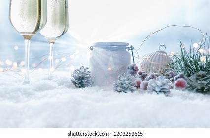 Christmas still life with champage glasses in snow and golden bokeh