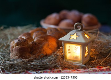 Christmas still life. Donuts and kalach on the table covered with hay. Traditional East Slavic bread.