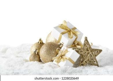 Christmas still life with golden balls, star and gift boxes lying on  winter snow on a white background with copy space. New Year and Christmas. Greeting card