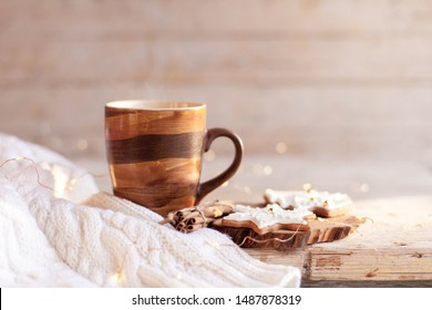 Christmas still life. Mug of hot steamy tea, gingerbread cookies at wooden background with glares. Cozy morning breakfast with homemade sweets and cup of coffee. Winter food, drinks, new year lights.