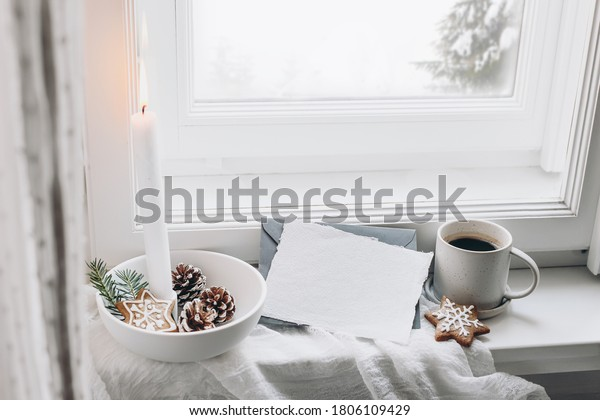 Christmas still life scene. Blank greeting card mockup. Cup of coffee, gingerbread cookies and fir tree branches. Burning candle in the ceramic candle holder. Seasonal photo. Scandinavian interior