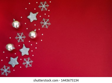 Christmas still life. Silver and gold decorative Christmas ornaments on a red background. Christmas, winter, new year concept. Flat lay, top view, copy space.