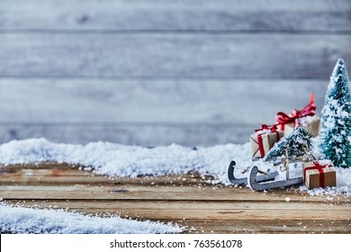 Christmas still life with a sled, tree and gift decorations on snow against rustic wood with background copy space and foreground space for product placement