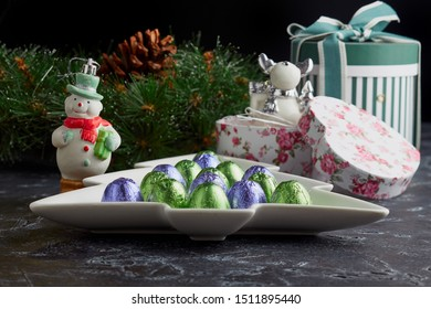 Christmas still life with sweets, gifts and souvenir figures of deer on the background of a wreath with cones on a dark background. Horizontal image.