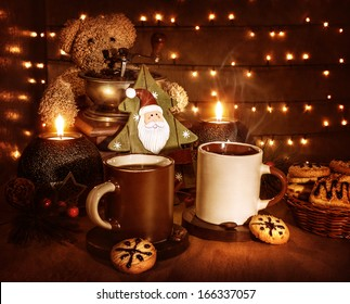Christmas still life, tasty traditional dessert, two cups of coffee with tasty cookie, teddy bear and little decorative Xmas tree toy with Santa Claus face