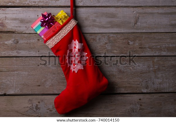 Christmas stocking filled with gifts. Red bag for presents from Santa Claus. Winter holidays and traditional decorations.
