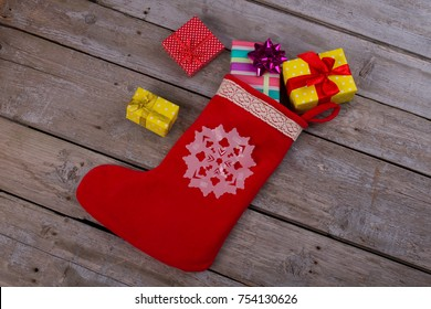 Christmas stocking and gift boxes dropped out it on wooden floor. Xmas presents, stocking fillers and stuffers.