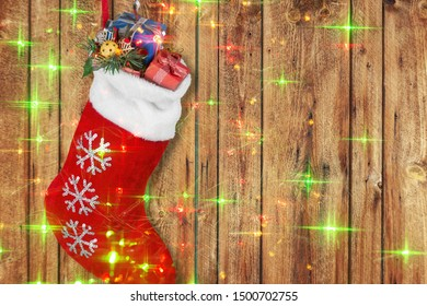 Christmas stocking with gifts hanging  on wooden wall