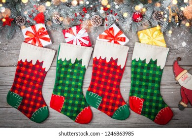 Christmas stocking hanging against wooden wall with gift presents and christmas decorstion