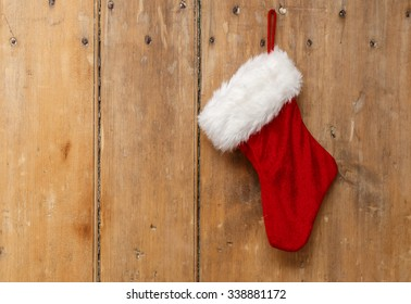 Christmas stocking hanging on an old pine wooden door
