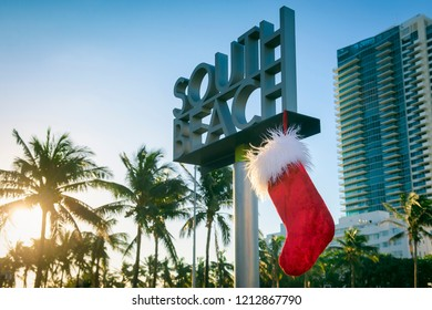 Christmas stocking hanging from a sign marking the entrance to South Beach, Miami, Florida, USA in morning sun with palm trees