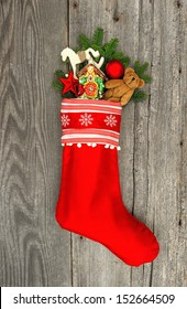 christmas stocking with nostalgic vintage toy decoration and pine branch over wooden background