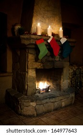 Christmas stocking on fireplace background. Chimney, candles and woodpile. (left view)