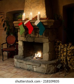 Christmas stocking on fireplace background. Chimney place, candles and woodpile. new year interior