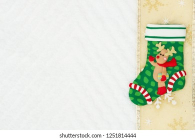 Christmas stocking with a reindeer with gold snowflake ribbon on white chevron textured fabric background that you can use as a mock up for your message for Christmas