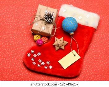 Christmas stocking sock shaped bag. Keep family traditions. Stocking stuffers idea. Santa stocking with christmas gift box. Christmas sock red background top view. Traditional christmas attribute.