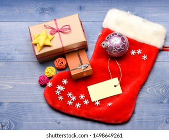 Christmas stocking sock shaped bag. Keep family traditions. Stocking stuffers idea. Stocking with christmas gift box. Christmas sock toned wood background top view. Traditional christmas attribute.