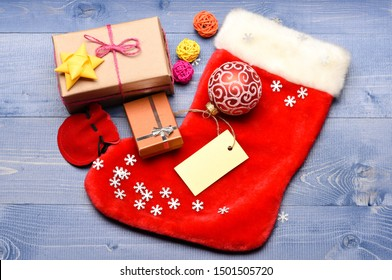 Christmas stocking sock shaped bag. Keep family traditions. Stocking with christmas gift box. Christmas sock toned wood background top view. Traditional christmas attribute. Stocking stuffers idea.