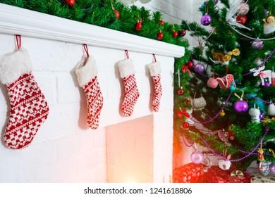 Christmas stockings hanging on fireplace near fir tree.