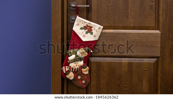 Christmas stockking on doorknob, wooden door.