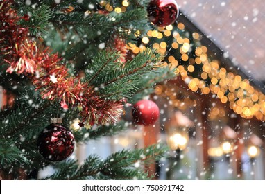 Christmas street decorations and falling snow - red ball, fir an