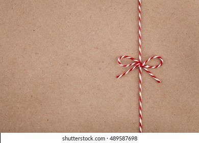 Christmas string or twine tied in bow on kraft paper texture
