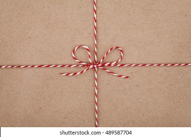 Christmas string or twine tied in a bow on kraft paper texture