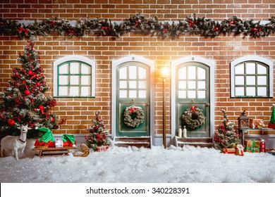 Christmas studio interior decorations with two wooden doors, street light, christmas tree, presents, brick wall, and windows.