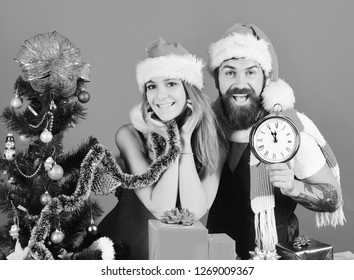 Christmas surprise and love concept. Man with beard and woman with happy faces on blue background. Mister and Missis Claus with red present near fir tree. Santa and sexy girl with clock and gift box