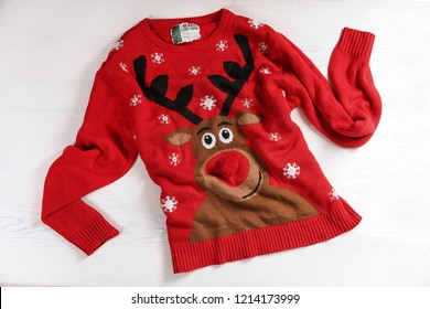 Christmas sweater with pattern on wooden background, top view