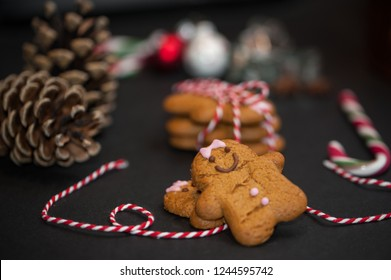 Christmas sweet gift concept: gingerman cookies, pinecones, candycane on black background with red-and-white string. Selective focus.