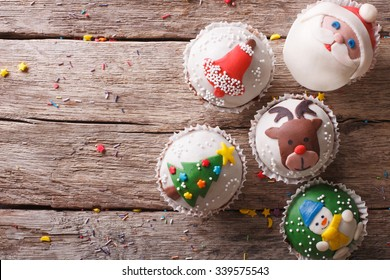Christmas sweets: cupcakes closeup on a wooden table. horizontal top view