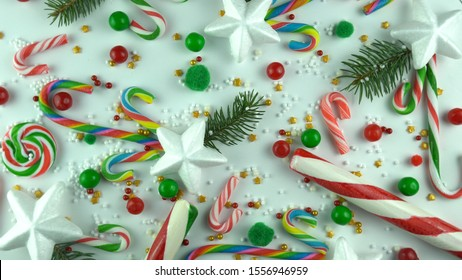 Christmas sweets mint candy canes close up. Traditional caramel lollipops top view concept. Holiday decoration background wit sweets gold, red sprinkles, snowflakes and real pine or fir tree branches